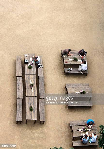 High Angle View Of People Sitting On Benches At Sidewalk Cafe