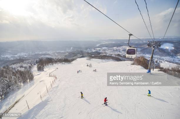 high angle view of people skiing on snowcapped mountain against sky - スキー板 ストックフォトと画像