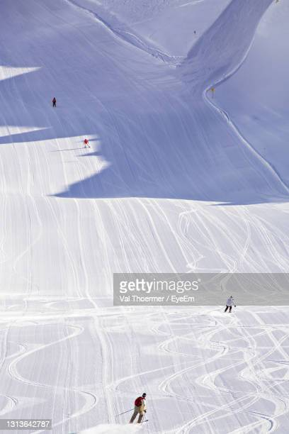 high angle view of people skiing on snowcapped mountain - val thoermer stock-fotos und bilder