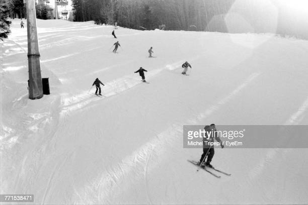 High Angle View Of People Skiing On Snowy Field