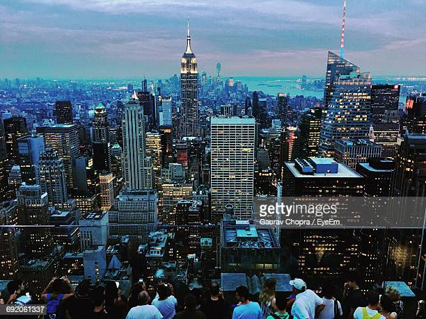 High Angle View Of People Standing By Illuminated Cityscape Against Cloudy Sky During Sunset
