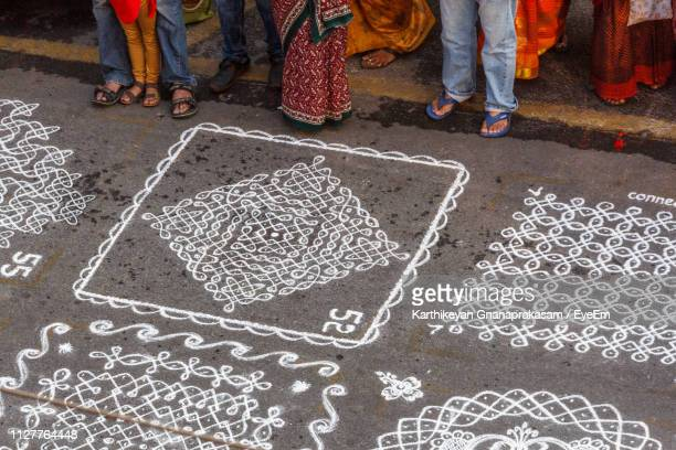 high angle view of people standing by rangolis on footpath during competition - rangoli stock pictures, royalty-free photos & images