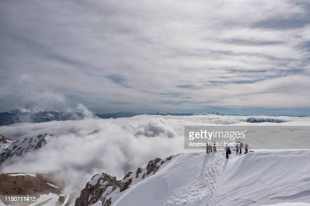 high angle view of people standing on snow covered mountain - andrea rizzi stockfoto's en -beelden