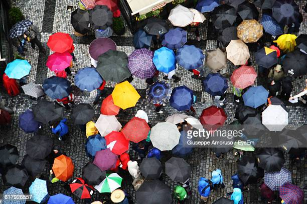 high angle view of people standing with umbrella on street during monsoon - heavy rain stockfoto's en -beelden