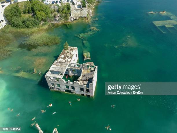 High Angle View Of People Swimming By Ruined Building In Sea