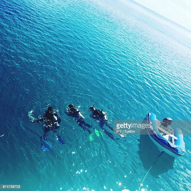 High Angle View Of People Swimming In Sea By Motorboat