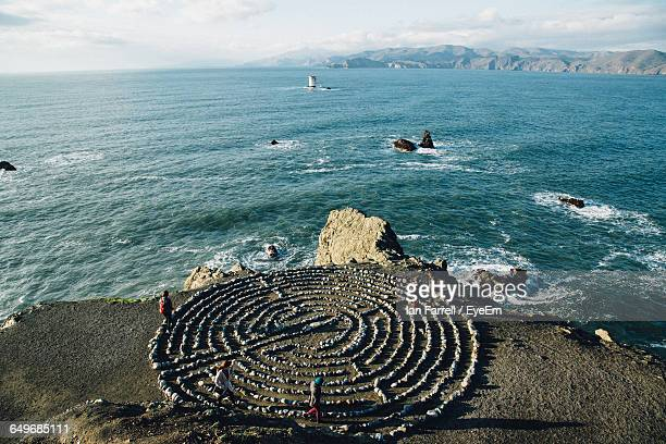 High Angle View Of People Taking Spiritual Journey Through Meditation Labyrinth At Coast