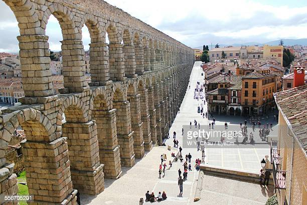 high angle view of people visiting historic ancient aqueduct in city - segovia stock photos and pictures