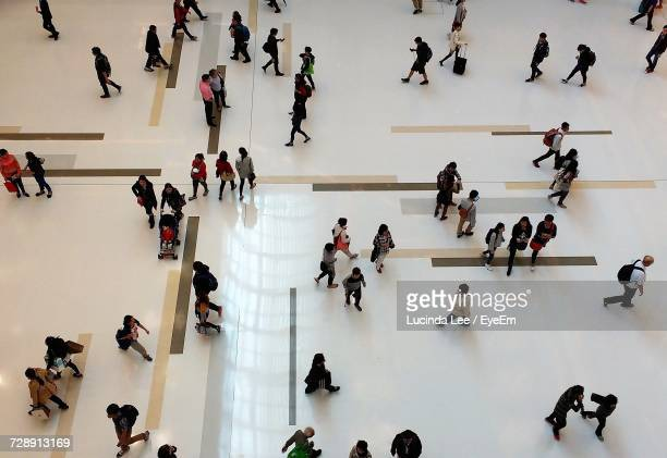 high angle view of people walking across atrium - shopping centre stock photos and pictures