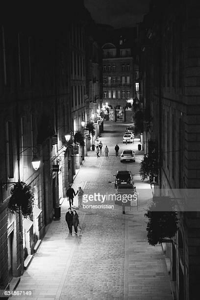 high angle view of people walking at illuminated street at night - bortes stock-fotos und bilder