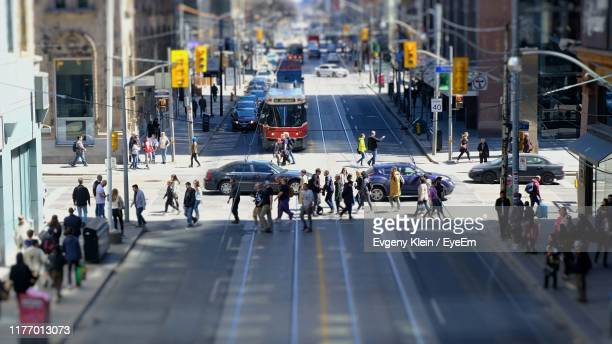 high angle view of people walking on city street - klein foto e immagini stock