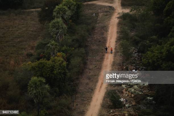 High Angle View Of People Walking On Dirt Road Amidst Field
