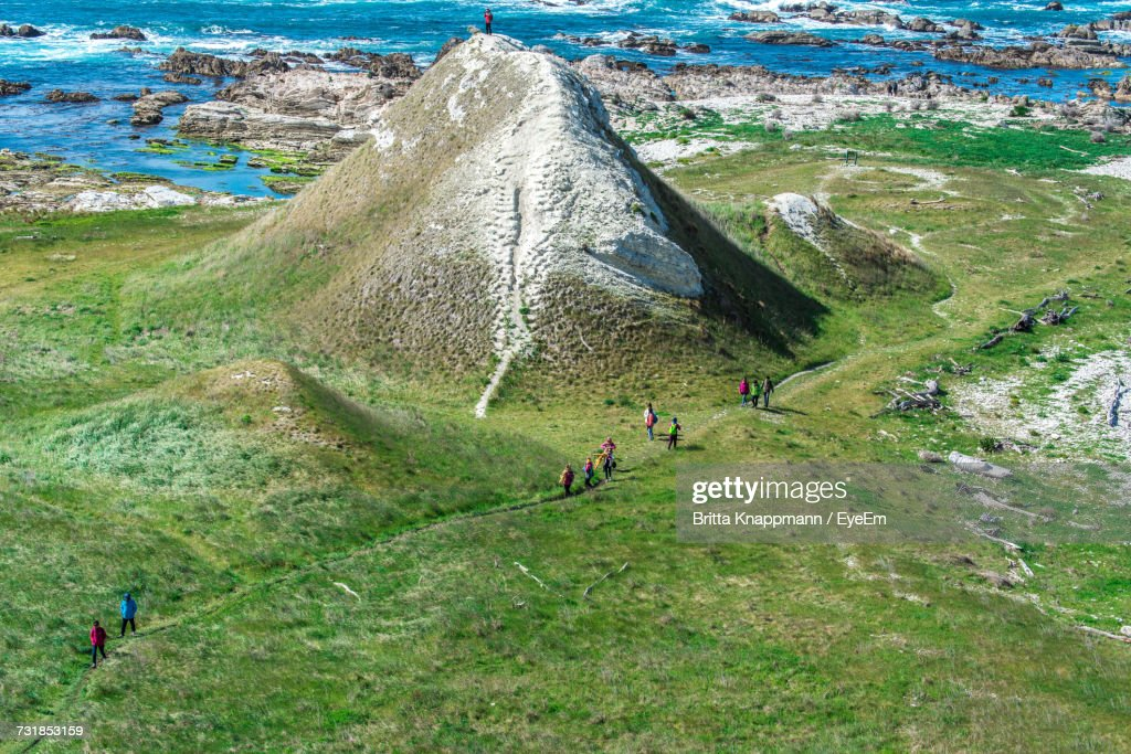 High Angle View Of People Walking On Field By Hill : Stock Photo