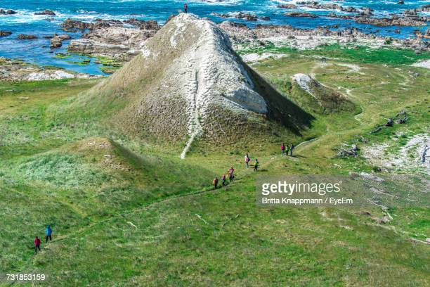 High Angle View Of People Walking On Field By Hill