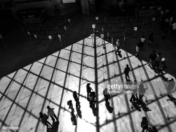 high angle view of people walking on floor with shadow of ceiling - paris noir et blanc photos et images de collection