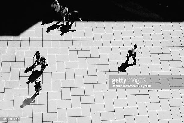High Angle View Of People Walking On Footpath During Sunny Day
