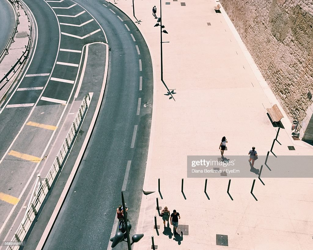 High Angle View Of People Walking On Sidewalk By Road : Stock Photo