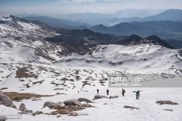 high angle view of people walking on snow covered land - andrea rizzi stockfoto's en -beelden