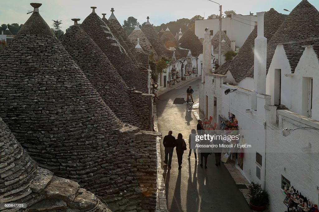 High Angle View Of People Walking On Street Amidst Trullo Houses With Conical Roofs In Alberobello : Stock Photo