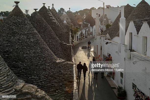 high angle view of people walking on street amidst trullo houses with conical roofs in alberobello - alessandro miccoli fotografías e imágenes de stock