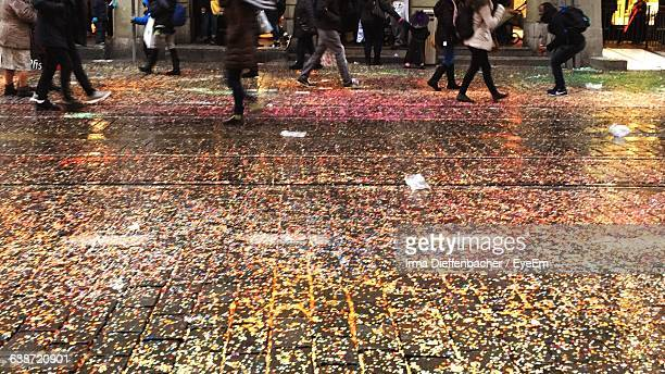 High Angle View Of People Walking On Wet Footpath With Confetti