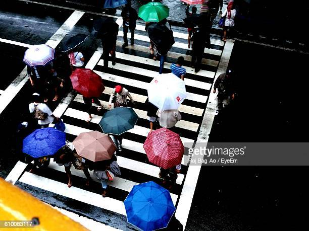 High Angle View Of People Walking On Zebra Crossing During Monsoon