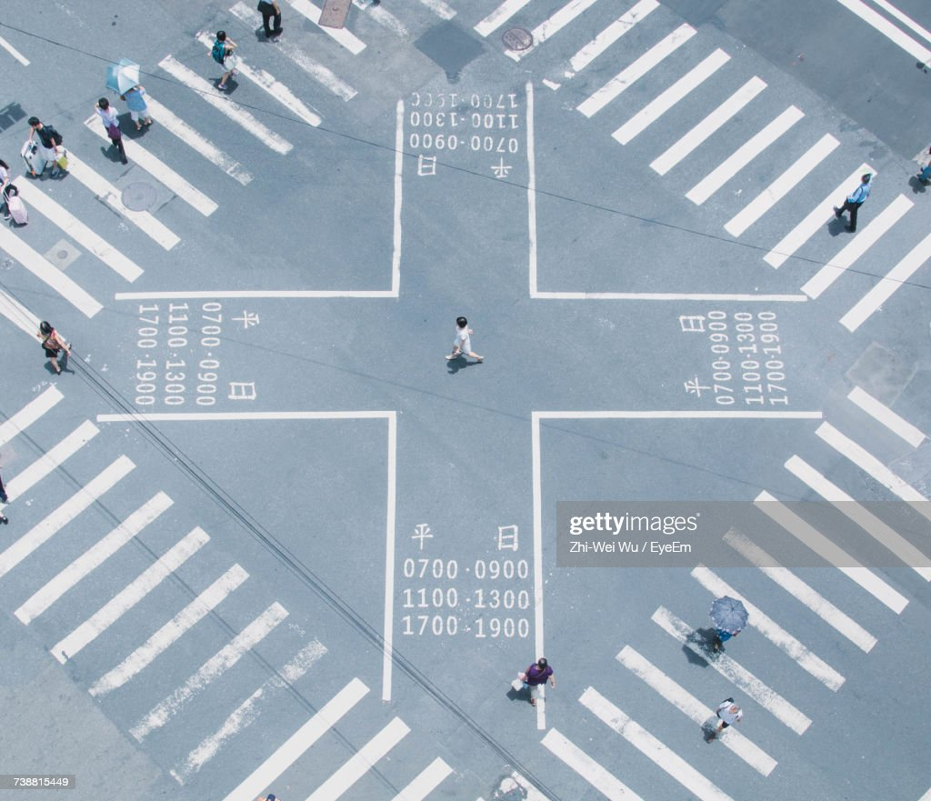High Angle View Of People Walking On Zebra Crossing : Stock Photo