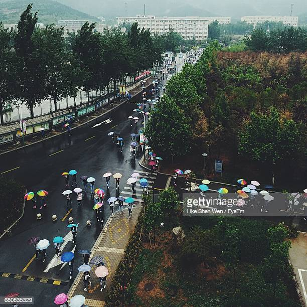 High Angle View Of People Walking With Umbrellas On City Street During Rainy Season