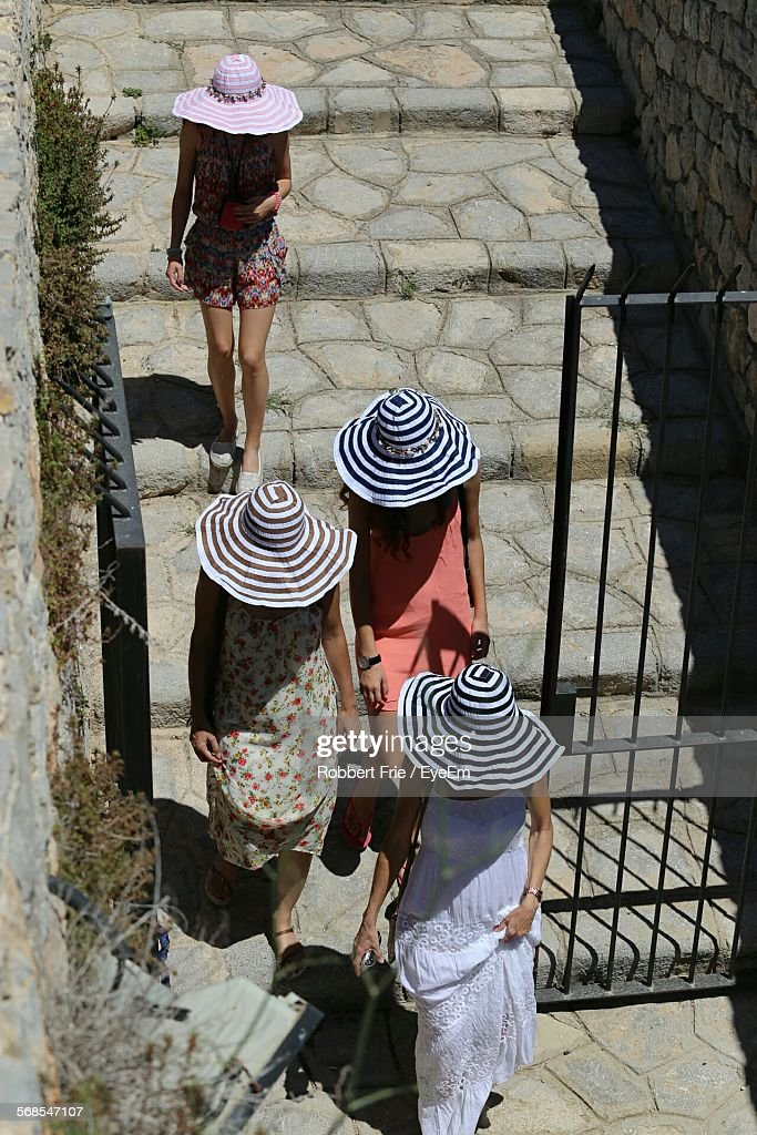 High Angle View Of People Wearing Sun Hats Walking On Footpath : Stock Photo