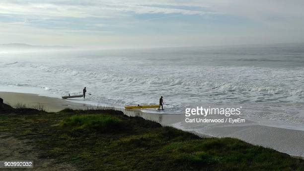 High Angle View Of People With Kayaks Walking At Beach