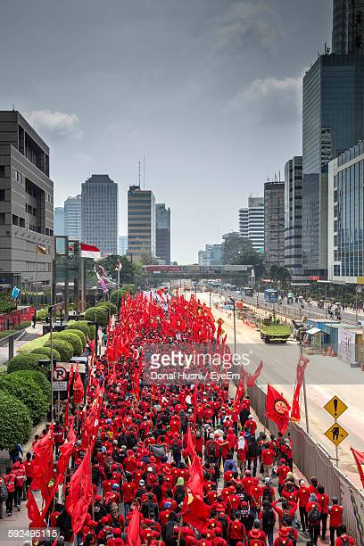 High Angle View Of People With Red Flags Walking In Parade