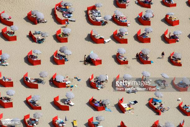 High Angle View Of People With Umbrella At Beach