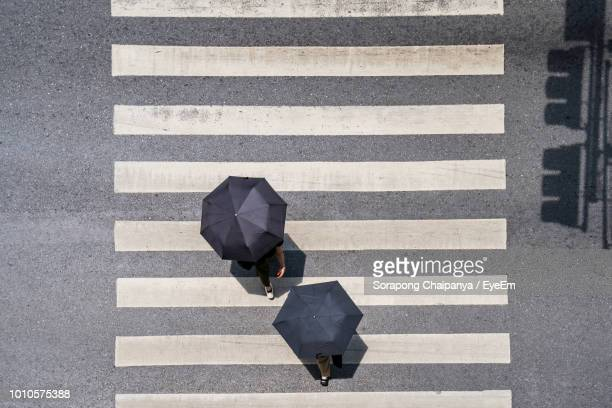high angle view of people with umbrellas crossing road in city - zebra crossing stock pictures, royalty-free photos & images
