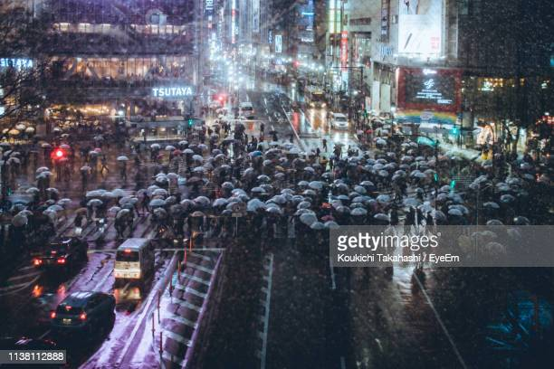 High Angle View Of People With Umbrellas On Street During Rainy Season At Night