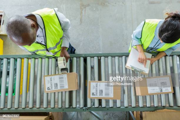 high angle view of people working in distribution warehouse - tape dispenser stock photos and pictures
