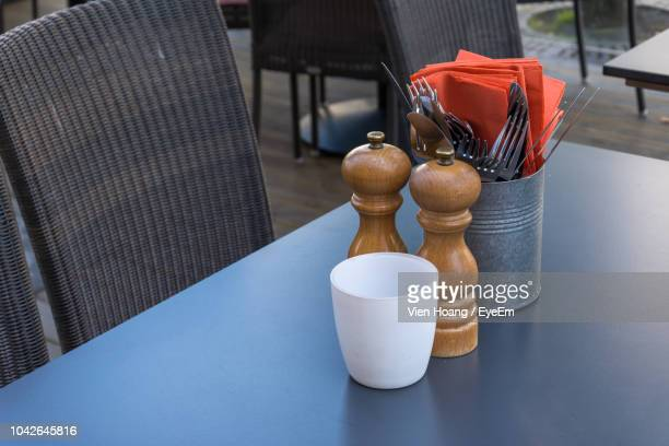 high angle view of pepper mills with cutlery and container on table in restaurant - pepper mill stock pictures, royalty-free photos & images