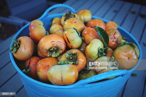High Angle View Of Persimmons In Basket On Table