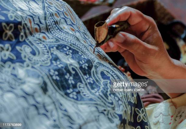 high angle view of person batik painting on fabric - indonesian cloth 個照片及圖片檔