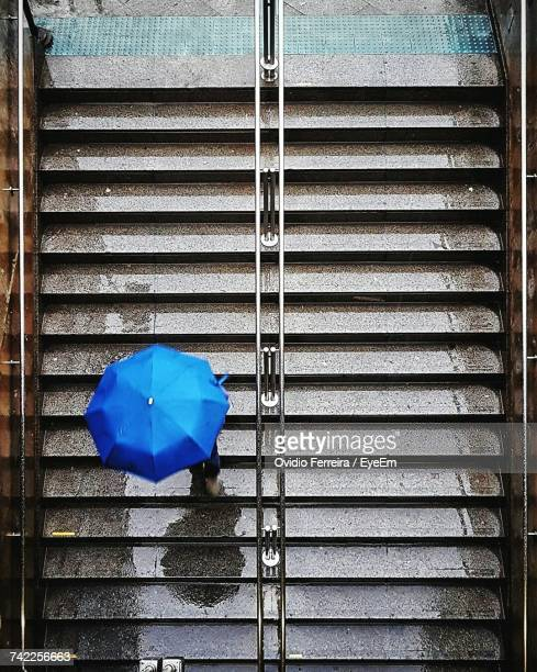 High Angle View Of Person Carrying Blue Umbrella While Moving Down On Steps During Rainy Season