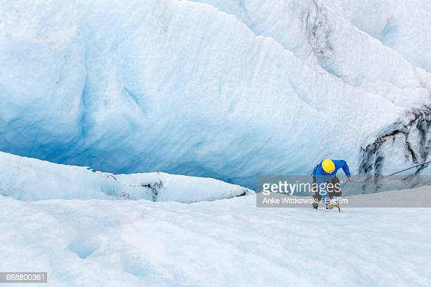 high angle view of person climbing on crevasse - crevasse stock photos and pictures