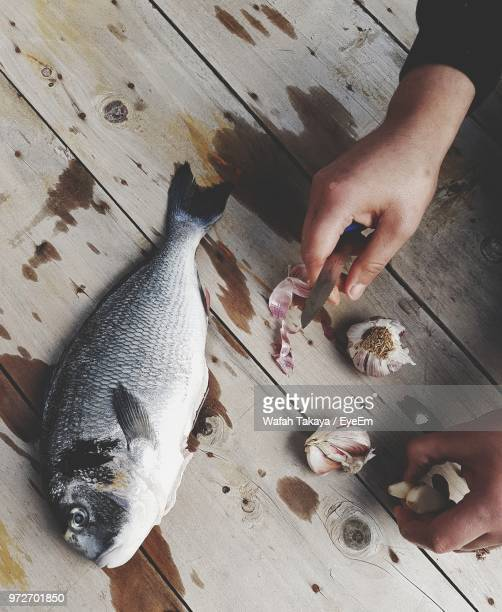 High Angle View Of Person Cutting Fish