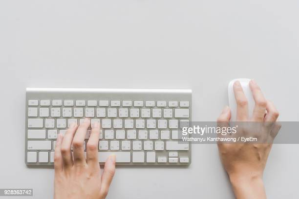 high angle view of person hands using computer mouse and keyboard - computer mouse stock pictures, royalty-free photos & images