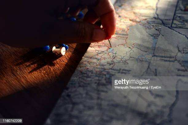high angle view of person holding thumbtack over map on table - push pin stock pictures, royalty-free photos & images