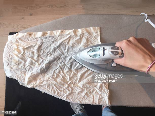 High Angle View Of Person Ironing Clothes At Home
