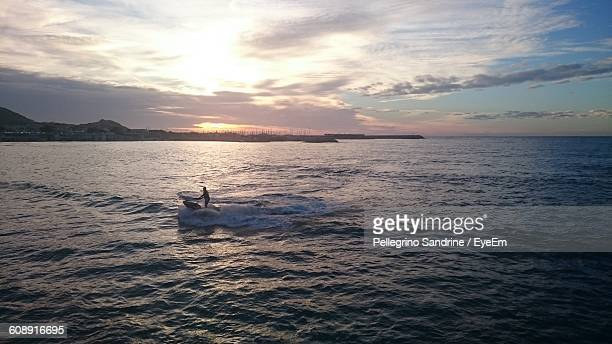 High Angle View Of Person Jet Boating On Sea Against Sky During Sunset