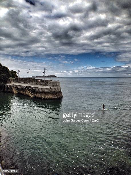 High Angle View Of Person Paddleboarding In Sea Against Cloudy Sky