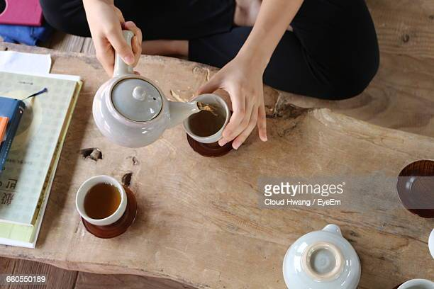 High Angle View Of Person Pouring Green Tea In Cup At Home