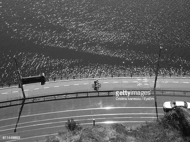 High Angle View Of Person Riding Bicycle On Road By Sea