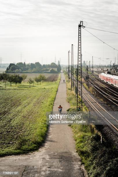 high angle view of person riding motor scooter by field on road - albrecht schlotter foto e immagini stock