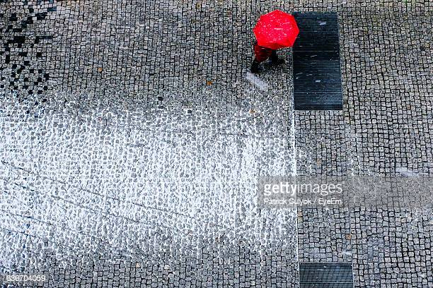 High Angle View Of Person Walking Below Red Umbrella On Footpath During Rainfall